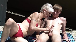 Kinky granny in constraints sucks a big hard penis of three young guy